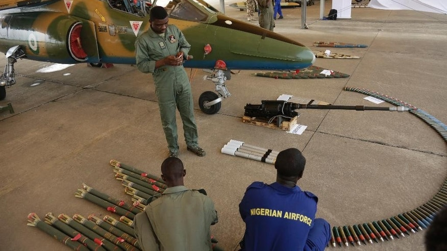 In this photo taken Saturday, April. 22, 2017 Nigeria Airforce officers, display Ammunitions next to a fighter jet during an event to celebrate 53rd Anniversary of Nigeria Airforce in Makurdi, Nigeria. (AP Photo/ Sunday Alamba)