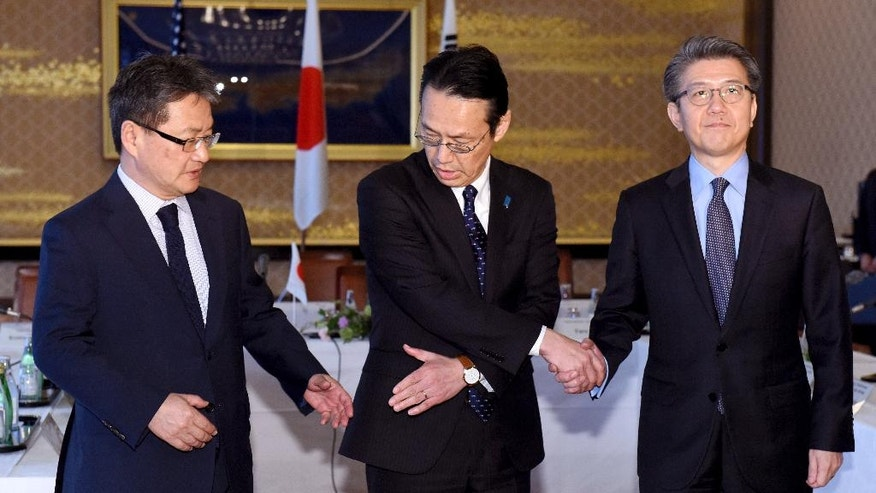 Chief nuclear negotiators from left to right, Joseph Yun, U.S. special representative for North Korea policy,  Kenji Kanasugi, director general of the Japanese Foreign Ministry's Asian and Oceanian Affairs Bureau, and Kim Hong-kyun, special representative for Korean Peninsula peace and security affairs at the South Korean Foreign Ministry, join hands before their meeting about North Korean issues at the Iikura Guesthouse in Tokyo Tuesday, April 25, 2017. North Korea marks the founding anniversary of its military on Tuesday, and South Korea and its allies are bracing for the possibility that it could conduct another nuclear test or launch an intercontinental ballistic missile for the first time.  (Toru Yamanaka/Pool Photo via AP)