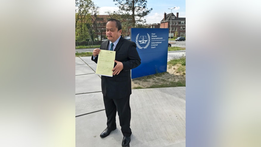 Lawyer Jude Sabio from the Philippines holds a 77-page file outside the International Criminal Court in The Hague, Netherlands, Monday, April 24, 2017. Sabio presented the file to prosecutors and asked to investigate his country's president Rodrigo Duterte for crimes against humanity for his alleged involvement in extrajudicial killings of suspected drug dealers and other crime suspects. (AP Photo/Mike Corder)