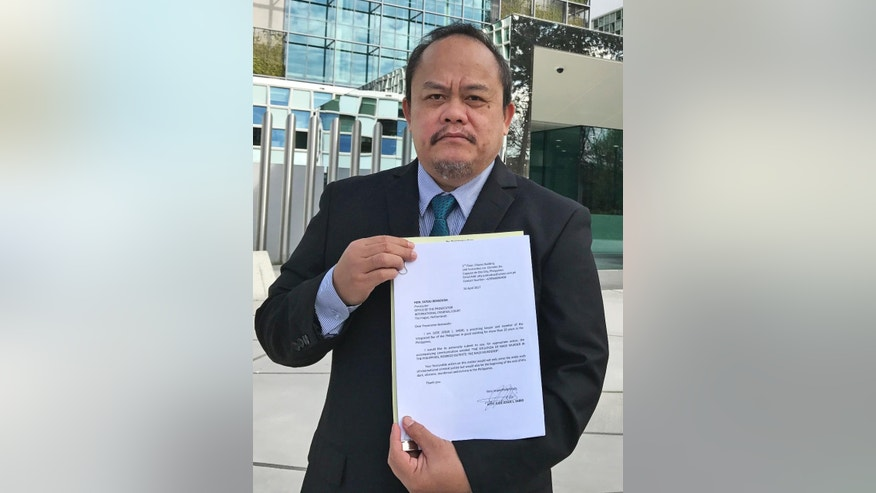Lawyer Jude Sabio from the Philippines poses for a portrait as he holds a 77-page file outside the International Criminal Court in The Hague, Netherlands, Monday, April 24, 2017. Sabio presented the file to prosecutors and asked to investigate his country's president Rodrigo Duterte for crimes against humanity for his alleged involvement in extrajudicial killings of suspected drug dealers and other crime suspects. (AP Photo/Mike Corder)