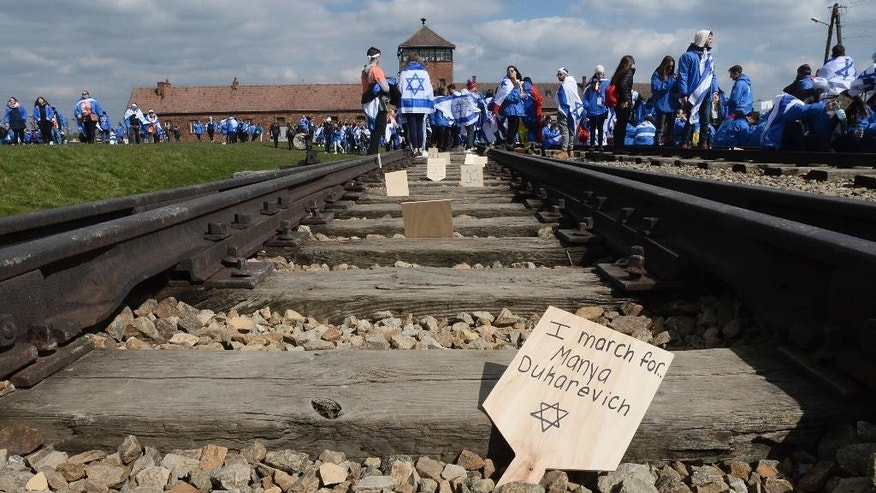 Participants of the yearly March of the Living place memory plaques on the rails in the former German Nazi Death Camp Auschwitz-Birkenau, in Brzezinka, Poland, Monday, April 24, 2017. Jews from Israel and around the world marched the 3km route from Auschwitz to Birkenau commemorating the Holocaust victims. (AP Photo/Alik Keplicz)