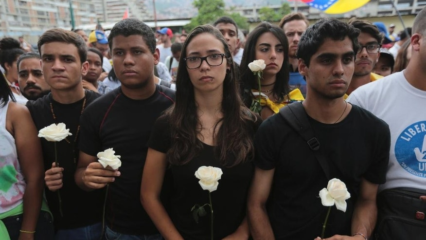 Protesters in black carry white flowers during a silent protest in homage to the at least 20 people killed in unrest generated after the nation's Supreme Court stripped congress of its last powers, a decision it later reversed, outside the Venezuelan Episcopal Conference in Caracas, Venezuela, Saturday, April 22, 2017. Saturday's protest is the latest mass gathering in a wave of tumult that has rocked the nation over the last three weeks as demonstrators continue to press for new elections. (AP Photo/Fernando Llano)