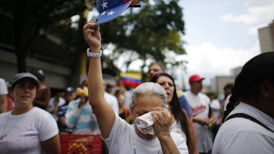 A woman wipes her face as she is overwhelmed with emotion during a silent protest in homage to the at least 20 people killed in unrest generated after the nation's Supreme Court stripped congress of its last powers, a decision it later reversed, as she marches to the Venezuelan Episcopal Conference in Caracas, Venezuela, Saturday, April 22, 2017. Saturday's protest is the latest mass gathering in a wave of tumult that has rocked the nation over the last three weeks as demonstrators continue to press for new elections. (AP Photo/Ariana Cubillos)