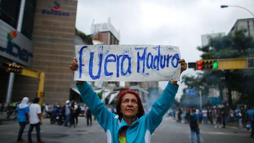 "A woman holds up a sign with a message that reads in Spanish: ""Out Maduro"" standing in the middle of a road during a protest against President Nicolas Maduro in Caracas, Venezuela, Monday, April 24, 2017. Weeks of anti-government unrest have claimed another victim as Venezuela's opposition prepares for another mass protest. (AP Photo/Ariana Cubillos)"