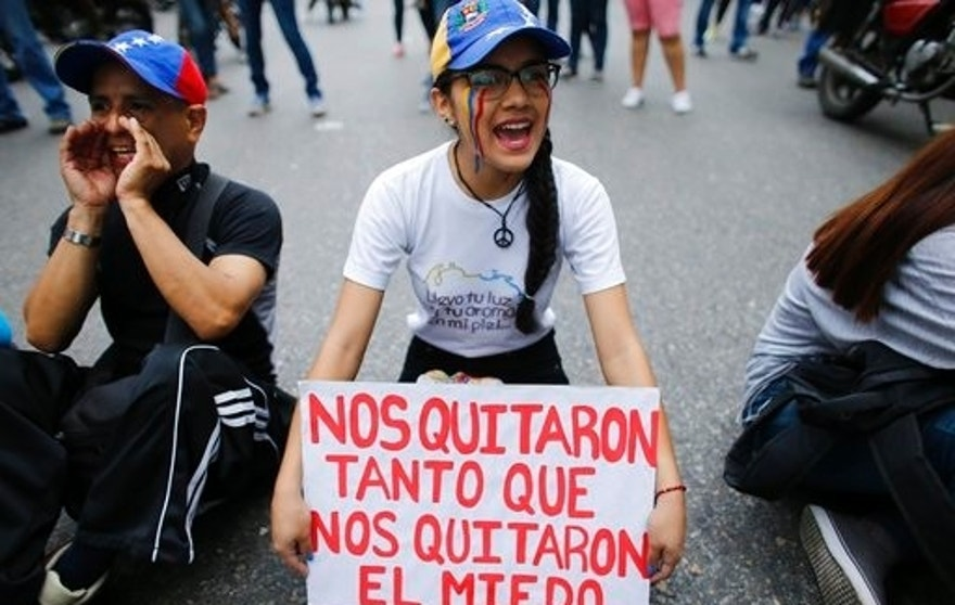"A woman holds up a sign with a message in Spanish that reads: ""They took away so much, that they took away our fear"" in the middle of a road during a protest against President Nicolas Maduro in Caracas, Venezuela, Monday, April 24, 2017. Weeks of anti-government unrest have claimed another victim as Venezuela's opposition prepares for another mass protest. (AP Photo/Ariana Cubillos)"