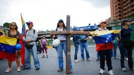 A woman holds as cross as she and fellow protesters block a highway during a protest against President Nicolas Maduro in Caracas, Venezuela, Monday, April 24, 2017. Weeks of anti-government unrest have claimed another victim as Venezuela's opposition prepares for another mass protest.  (AP Photo/Ariana Cubillos)