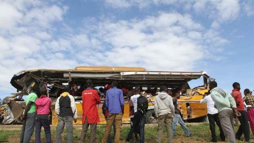 Kenyans look at the wreckage of a Buscar Bus Company vehicle that was involved in a road accident at Kambuu area in Makueni, along the Nairobi-Mombasa highway Tuesday, April 25. 2017. Kenyan police say 27 people have been killed in a collision between a passenger bus and a trailer truck. (AP Photo)