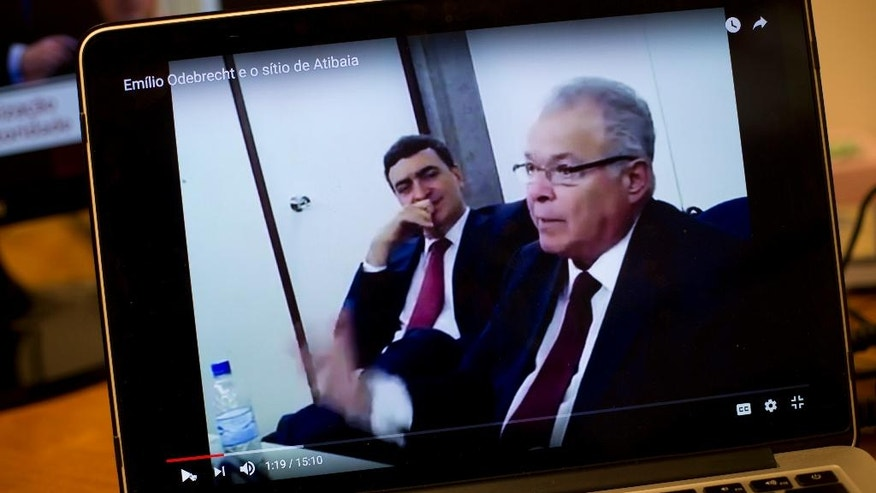 This April 19, 2017 photo shows a computer screen streaming a video of Emilio Odebrecht, right, during his plea bargain deposition, in Rio de Janeiro, Brazil. Often grinning on camera, Odebrecht, former CEO of the Brazilian constructor at the center of the world's biggest corruption scandal, spoke frankly about the hundreds of millions in bribes and illegal financing that his company put into pockets and campaign coffers. (AP Photo/Silvia Izquierdo)