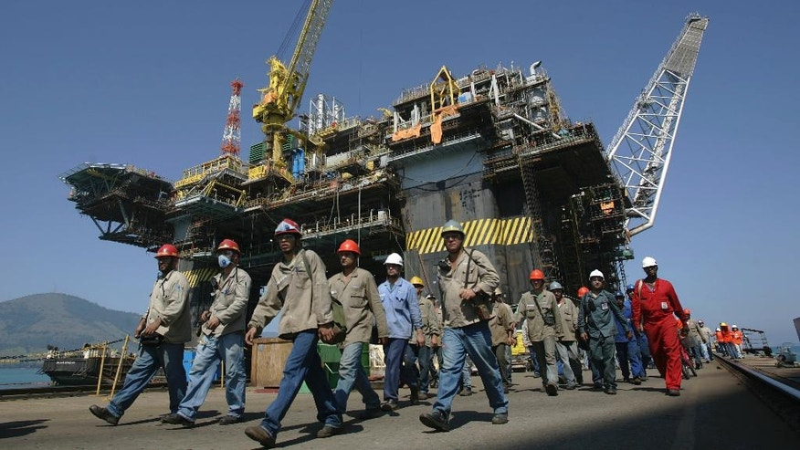 FILE - In this Aug. 21, 2008 file photo, workers walk in front of the P-51 oil rig of Brazil's state-run oil company Petrobras, in Angra dos Reis, Rio de Janeiro, Brazil. Founded in 1944, Odebrecht's relationship with politicians dates back to the 1950s, when the board of state-run oil giant Petrobras was made of military staff from the state of Bahia, where the constructor held its headquarters for decades. (AP Photo/Ricardo Moraes, File)