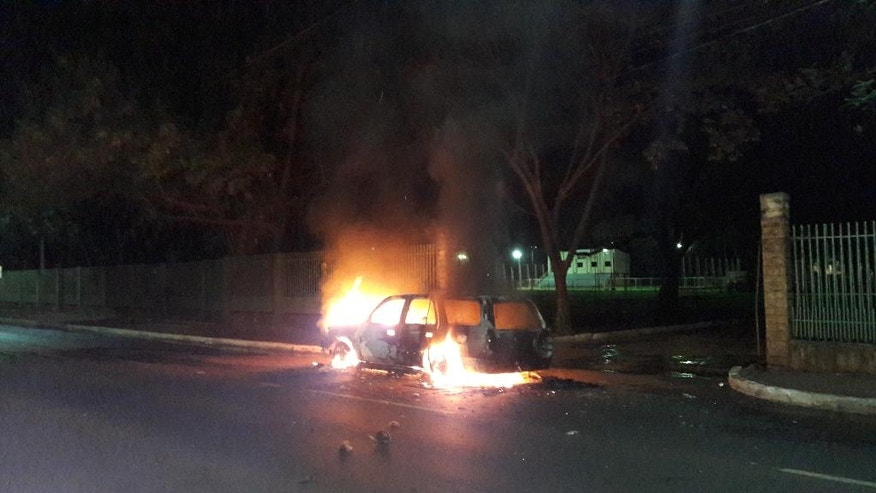 A vehicle burns after thieves set it on fire during their escape in Ciudad del Este, Paraguay, Monday, April 24, 2017. According to reports, dozens of attackers armed with assault rifles used explosives to blast open the vault of an armored car company early Monday and apparently escaped by boat into Brazil with a haul of cash. (Mariana Ladaga/Diario ABC Color via AP)