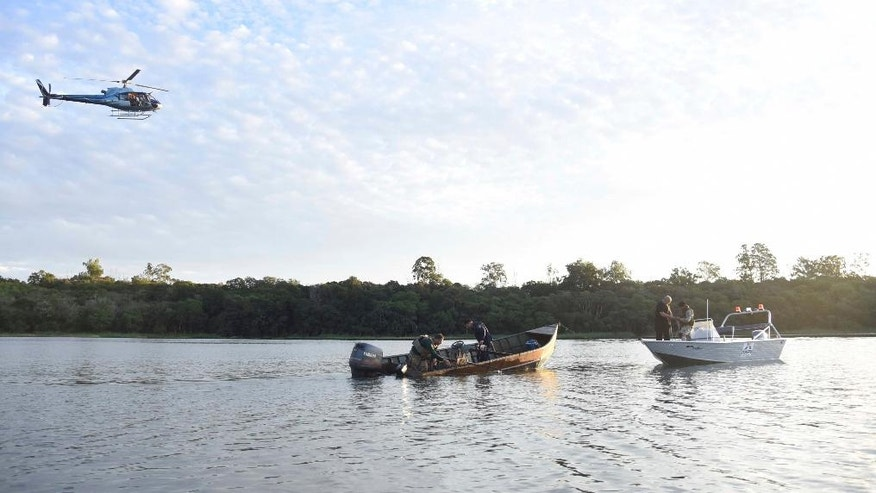 "Police inspect a boat that assailants used to escape after a massive armored car company robbery, in the Parana River, border with Brazil and Paraguay, Monday, April 24, 2017. A gang of over 50 armed bandits stole several million dollars from a vault in Paraguay, in what local officials are dubbing the ""robbery of the century"". The culprits, who police said were from Brazil, killed one police officer during the Monday raid. (Roberto Zarza/Diario ABC Color via AP)"