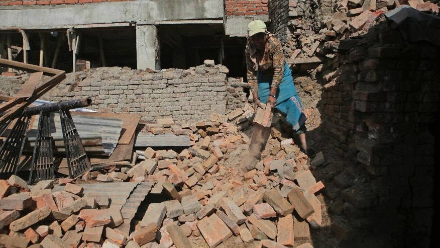 In this April 24, 2017, photo, a Nepalese woman collects bricks from a destroyed house in Bhaktapur, Nepal. Nearly everything was lost two years ago, when a terrifying earthquake rattled the Himalayan nation on April 25, 2015, killing more than 9,000 people and toppling nearly a million homes nationwide. The government has been criticized for moving slowly in dispersing funds that would allow people to rebuild on their own. (AP Photo/Niranjan Shrestha)
