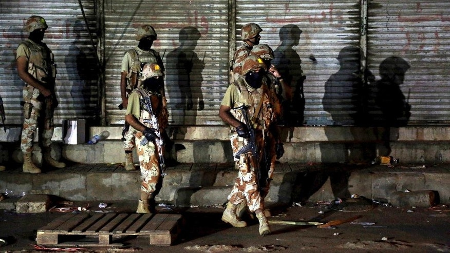 Pakistani paramilitary troops take up positions during a gunbattle with militants in Karachi, Pakistan Tuesday, April 25, 2017. Pakistani paramilitary forces raided an apartment in the port city of Karachi, acting on a tip that militants were hiding there, police officer Aurangzeb Khattak said. The paramilitary force said that after a seven-hour siege, three militants, including a woman, blew themselves up inside the apartment. (AP Photo/Shakil Adil)
