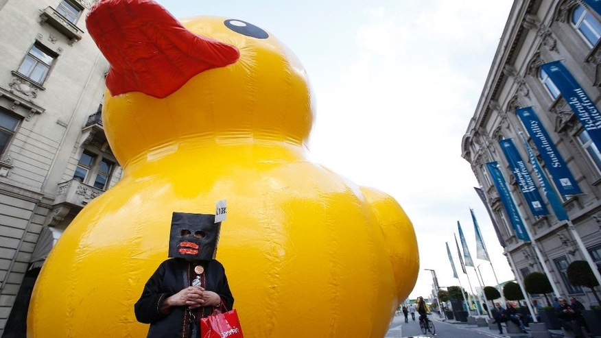 A woman wearing a mask stands in front of a giant yellow rubber duck, a mascot of a group of people criticizing the Belgrade waterfront plan, during a protest in Belgrade, Serbia, Tuesday, April 25, 2017. Several thousand people have rallied in the Serbian capital, Belgrade, one year after a mysterious demolition in an area marked for a United Arab Emirates-financed real estate project. (AP Photo/Darko Vojinovic)