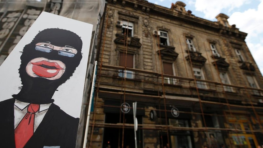 A protester holds a banner depicting masked Serbian Prime Minister Aleksandar Vucic during a protest in Belgrade, Serbia, Tuesday, April 25, 2017. Several thousand people have rallied in the Serbian capital, Belgrade, one year after a mysterious demolition in an area marked for a United Arab Emirates-financed real estate project.  (AP Photo/Darko Vojinovic)