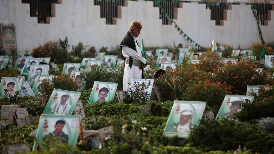 FILE -- In this Sept. 12, 2016 file photo, a Yemeni man offers prayers at the portrait adorned grave of his relative who was killed in the ongoing conflict in Yemen, in Sanaa, Yemen. The U.N. secretary-general and high-ranking government officials from dozens of countries are meeting Tuesday, April 25, 2017,  in Geneva to drum up funds for war-torn Yemen. The impoverished Mideast country on the tip of the Arabian Peninsula is considered the world's greatest humanitarian crisis. Yemen's war has killed more than 10,000 civilians. (AP Photo/Hani Mohammed, File)