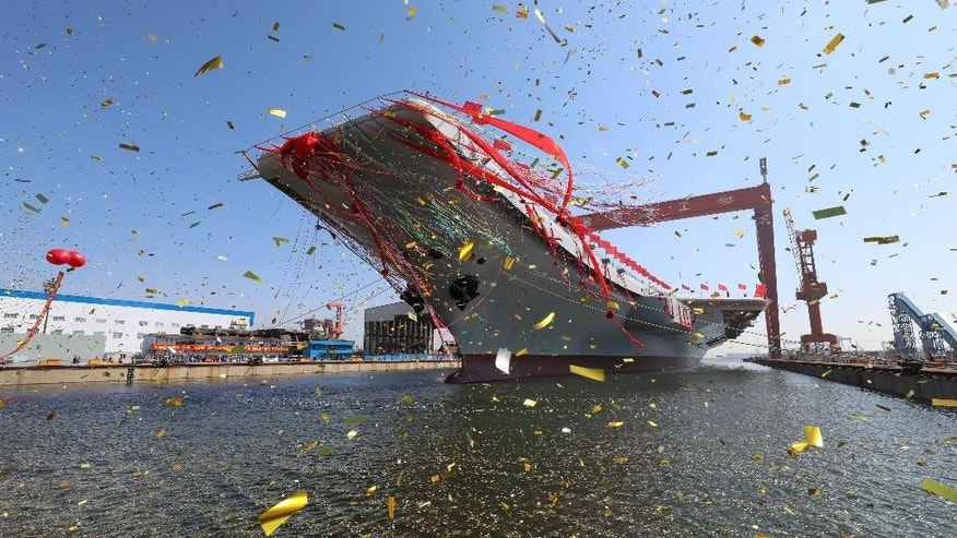 In this photo released by China's Xinhua News Agency, a newly-built aircraft carrier is transferred from dry dock into the water at a launch ceremony at a shipyard in Dalian in northeastern China's Liaoning Province, Wednesday, April 26, 2017. China launched its first aircraft carrier built entirely on its own on Wednesday, in a demonstration of the growing technical sophistication of its defense industries and determination to safeguard its maritime territorial claims and crucial trade routes. (Li Gang/Xinhua via AP)
