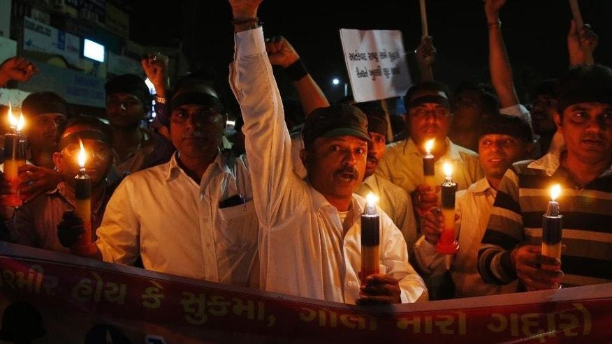 Indians shout slogans condemning Monday's Maoist attack in Chhattisgarh's Sukma district, as they light candles to pay tribute to the killed soldiers in Ahmadabad, India, Tuesday, April 25, 2017. Maoist rebels killed at least 25 Indian paramilitary soldiers and injured six others in their stronghold in central India on Monday in one of the worst attacks on the country's security forces in recent years. (AP Photo/Ajit Solanki)