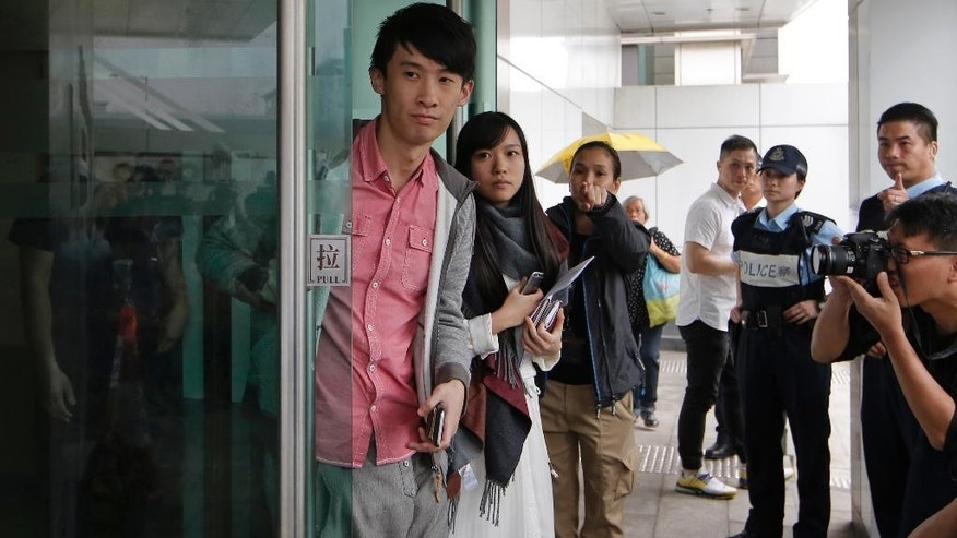 Pro-independence lawmakers Sixtus Leung, left, and Yau Wai-ching, second frm left, walk out of a police station after being released on bail in Hong Kong, Wednesday, April 26, 2017. Hong Kong police arrested two disqualified pro-independence lawmakers over their attempts to barge into the legislature last year in a dispute over their oaths. (AP Photo/Kin Cheung)
