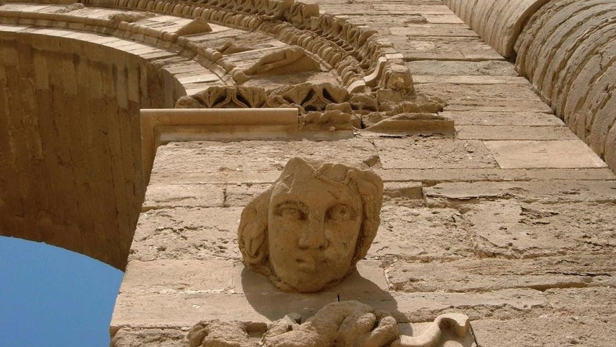 FILE - In this July 27, 2005 file photo, a sculpture of a female face stares down at visitors, in the Hatra ruins, 320 kilometers (200 miles) north of Baghdad, Iraq. Iraqi paramilitary forces said Wednesday, April 26, 2017, that they have captured Hatra, a 2,000-year-old historical site near the northern city of Mosul, where U.S.-backed forces have been battling the Islamic State group for months. (AP Photo/Antonio Castaneda, File)