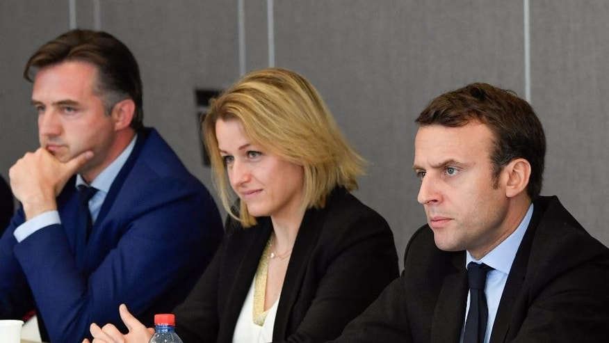 French presidential election candidate Emmanuel Macron, right, listens to union representatives from the Whirlpool plant next to National Assembly member Barbara Pompili, center, at the Chamber of Commerce and Industry in Amiens, northern France, Wednesday April 26, 2017. Man at left is unidentified. (Eric Feferberg, Pool via AP)