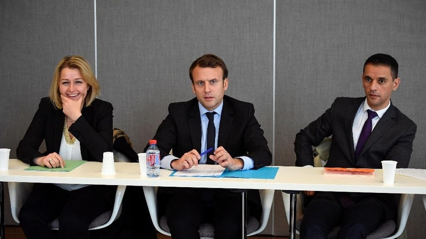 French presidential election candidate Emmanuel Macron, center, listens to union representatives from the Whirlpool plant next to National Assembly member Barbara Pompili, left,, at the Chamber of Commerce and Industry in Amiens, northern France, Wednesday April 26, 2017. Man at right is unidentified. (Eric Feferberg, Pool via AP)