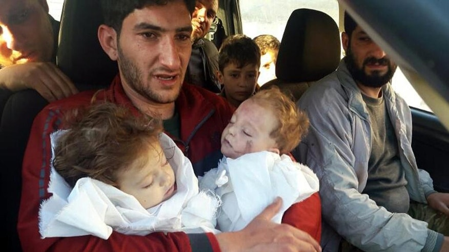 "FILE -- In this Tuesday April 4, 2017 file photo, Abdel Hameed Alyousef, 29, holds his twin babies who were killed during a suspected chemical weapons attack, in Khan Sheikhoun in the northern province of Idlib, Syria. France's foreign minister says chemical analysis of samples taken from a deadly sarin gas attack in Syria shows that the nerve agent used ""bears the signature"" of President Bashar Assad's government and shows it was responsible. Jean-Marc Ayrault says France now knows ""from sure sources"" that ""the manufacturing process of the sarin that was sampled is typical of the method developed in Syrian laboratories."" But Kremlin promptly denounced the French report. (Alaa Alyousef via AP, File)"