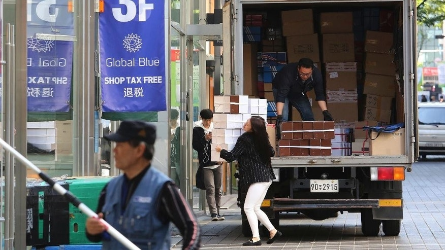An employee carries boxes in Seoul, South Korea, Thursday, April 27, 2017. Asia's fourth-largest economy, grew at the fastest clip in nearly a year thanks to recovery in exports, the central bank said Thursday, despite a backlash from Chinese consumers over the deployment of a U.S. missile defense system. (AP Photo/Ahn Young-joon)