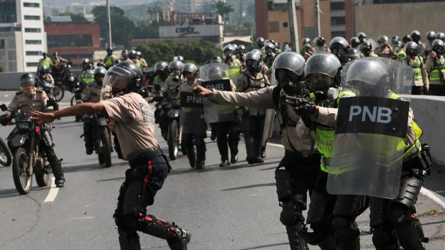 Police officers charge an anti-government protesters in Caracas, Venezuela, Monday, April 24, 2017. Thousands of people shut down the capital city's main highway to express their disgust with the socialist administration of President Nicolas Maduro. Demonstrators in least a dozen other cities also staged sit-ins as the protest movement is entering its fourth week. (AP Photo/Fernando Llano)