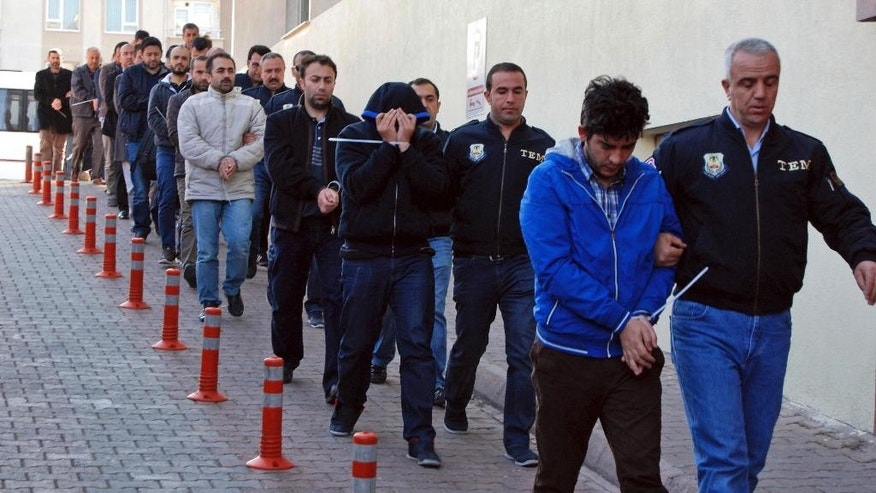 Police officers escort people, arrested because of suspected links to U.S.-based cleric Fethullah Gulen, in Kayseri, Turkey, Wednesday, April 26, 2017. Police launched simultaneous operations across the country on Wednesday, detaining hundreds of people with suspected links to U.S.-based cleric Fethullah Gulen. The suspects are allegedly Gulen operatives who directed followers within the police force. (Olay Duzgun/DHA-Depo Photos via AP)