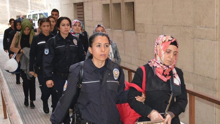 Turkish police officers escort women into a courthouse in Bursa, Turkey, arrested on suspicion of having links with U.S.-based cleric Fethullah Gulen, Thursday, April 27, 2017.   Twenty-five people were detained in Turkey and more than 200 police officers temporarily suspended from their jobs Thursday for suspected links to U.S.-based cleric Fethullah Gulen, following a massive sweep the day before in connection with  last summer's failed coup attempt. Gulen has denied the accusations. (Berktug Oncu/DHA-Depo Photos via AP)