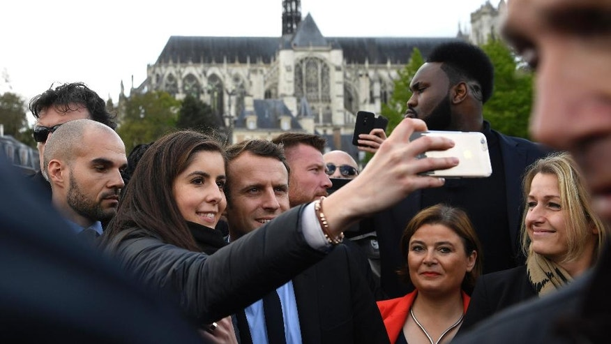French centrist presidential election candidate Emmanuel Macron poses for a selfie outside the cathedral of Amiens, northern France, Wednesday April 26, 2017. Battling for France's blue-collar vote and employing all of her political guile, far-right presidential candidate Marine Le Pen upstaged her rival Macron by making a surprise campaign stop to a home appliance factory threatened with closure. (AP Photo/Eric Feferberg, Pool via AP)