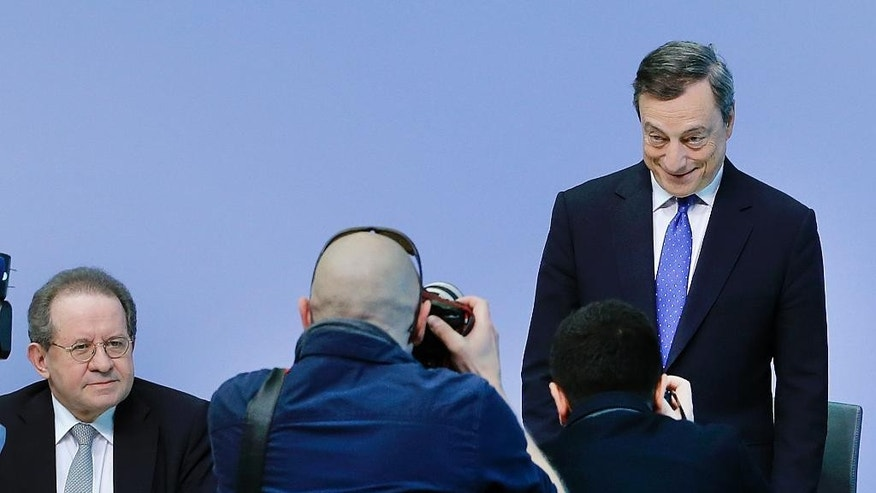 President of the European Central Bank Mario Draghi, right, poses for photographers prior to a news conference in Frankfurt, Germany, Thursday, April 27, 2017. At left his deputy Vitor Constancio. (AP Photo/Michael Probst)
