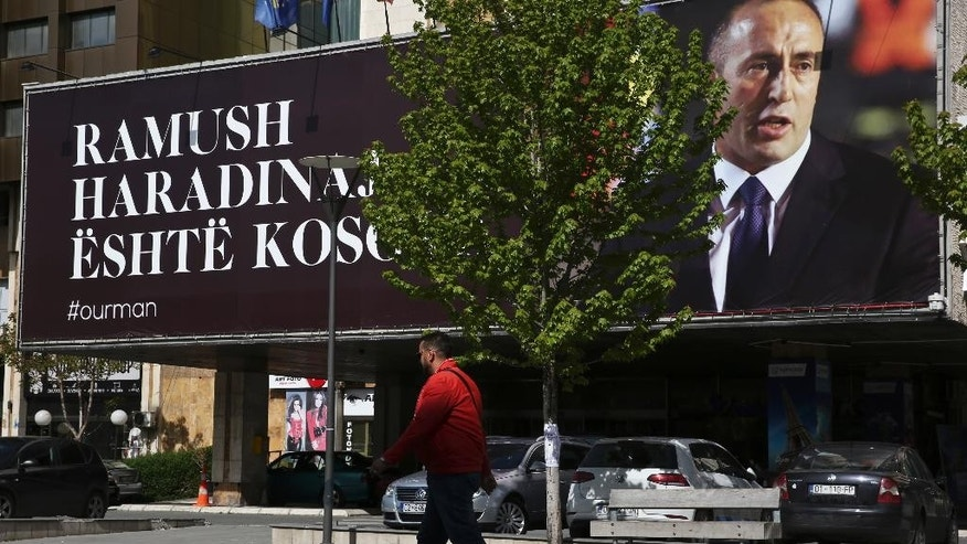 "A Kosovar walks past a giant banner reading in Albanian ""Ramush Haradinaj is Kosova"" with a portrait of former Kosovo Prime Minister Ramush Haradinaj in capital Pristina, Kosovo Thursday, April 27, 2017. A French court has refused to extradite Haradinaj to Serbia to face war crimes charges. The court in the northeastern town of Colmar said Haradinaj has been released. (AP Photo/Visar Kryeziu)"