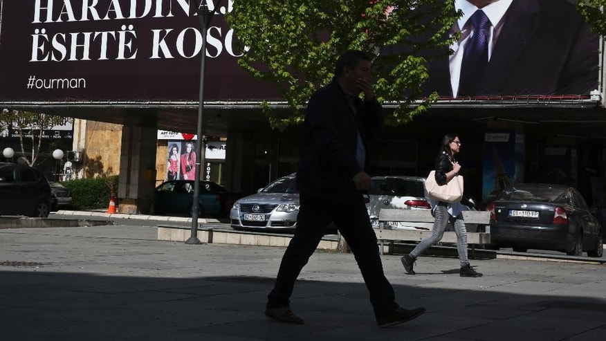 "Kosovars walk past a giant banner reading in Albanian ""Ramush Haradinaj is Kosova"" with a portrait of former Kosovo Prime Minister Ramush Haradinaj in capital Pristina, Kosovo Thursday, April 27, 2017. A French court has refused to extradite Haradinaj to Serbia to face war crimes charges. The court in the northeastern town of Colmar said Haradinaj has been released. (AP Photo/Visar Kryeziu)"