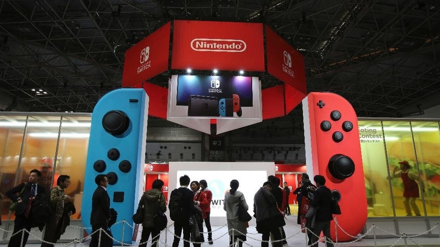 FILE - In this Friday, Jan. 13, 2017 file photo, journalists wait outside the venue for the presentation of the new Nintendo Switch in Tokyo. Nintendo Co. says its new Switch, a hybrid game machine that works as both a console and a tablet, is selling well, helping the Kyoto-based company behind the Super Mario and Pokemon franchises trim its quarterly losses. Nintendo said Thursday, April 27, 2017,  it has sold 2.74 million Switch machines and 5.46 million units of Switch software since sales began in March.(AP Photo/Koji Sasahara, File)