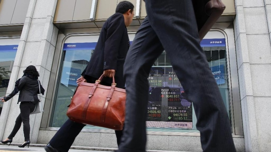 People walk past an electronic stock board showing Japan's Nikkei 225 index at a securities firm in Tokyo, Friday, April 28, 2017. Japan reports that its manufacturing output and household spending fell in March, while the jobless rate remained at a 22-year low. The data released Friday generally were slightly weaker than analysts had forecast, though the outlook for the world's third-largest economy remained upbeat. (AP Photo/Shuji Kajiyama)