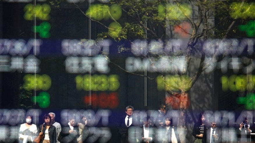 People waiting for the green light to cross the street are reflected on the electronic stock board showing global stock index at a securities firm in Tokyo, Friday, April 28, 2017. Japan reports that its manufacturing output and household spending fell in March, while the jobless rate remained at a 22-year low. The data released Friday generally were slightly weaker than analysts had forecast, though the outlook for the world's third-largest economy remained upbeat. (AP Photo/Shuji Kajiyama)