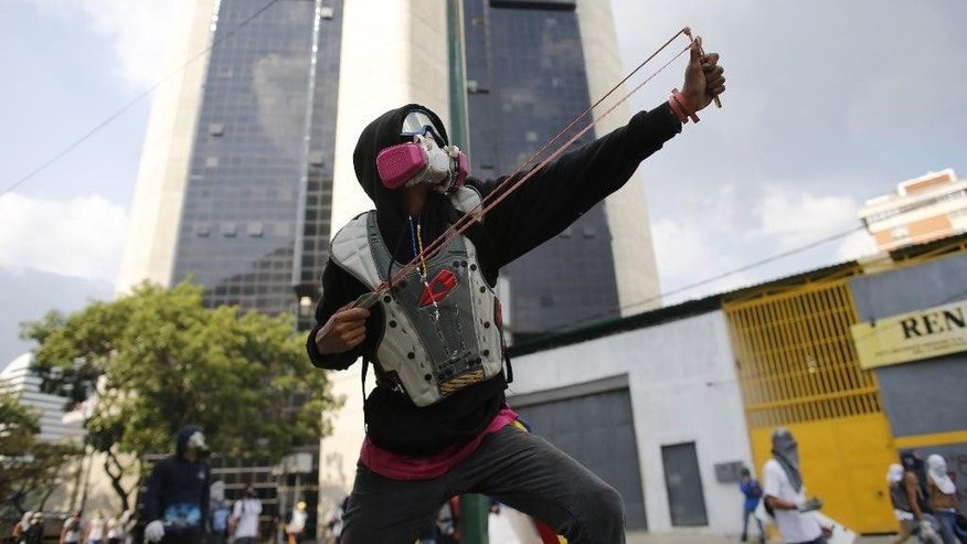 An opponent of President Nicolas Maduro aims his slingshot during protests as security forces block protesters from reaching the national ombudsman office in Caracas, Venezuela, Wednesday, April 26, 2017. Hundreds of thousands of Venezuelans have flooded the streets over the last month to demand an end to Maduro's presidency. (AP Photo/Ariana Cubillos)