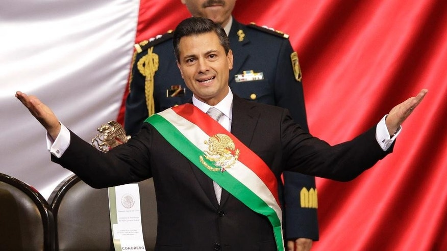 FILE - In this Dec. 1, 2012 file photo, Mexico's incoming President Enrique Pena Nieto of the Institutional Revolution Party, PRI, spreads out his arms after being sworn in at the inauguration ceremony in National Congress, in Mexico City. The PRI ruled Mexico for 71 years, despite accusations of stolen or bought elections, before being ousted in 2000 voting. When it returned to power in 2012 under President Pena Nieto, its leaders couldn't stop talking about how their party had changed. (AP Photo/Alexandre Meneghini, File)
