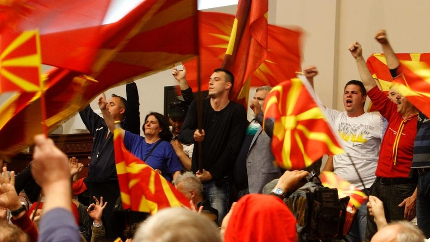 Protestors wave national flags after entering into the parliament building in Skopje, Macedonia, Thursday, April 27, 2017.  Scores of protesters have broken through a police cordon and entered Macedonian parliament to protest the election of a new speaker despite a months-long deadlock in talks to form a new government. (AP Photo/Boris Grdanoski)