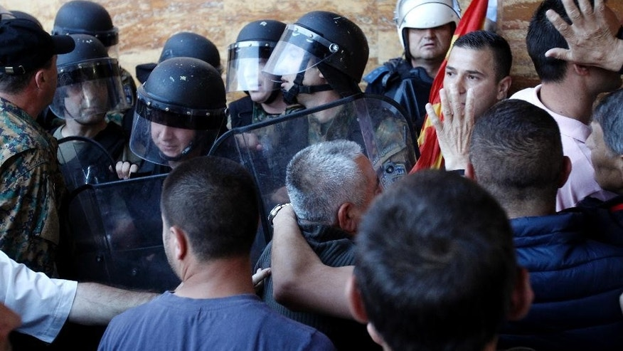 Police try to block the protestors to enter into the parliament building in Skopje, Macedonia, Thursday, April 27, 2017. Some scores of protesters broke through a police cordon and entered the Macedonian parliament to protest the election of a new speaker despite a months-long deadlock in talks to form a new government. (AP Photo/Boris Grdanoski)