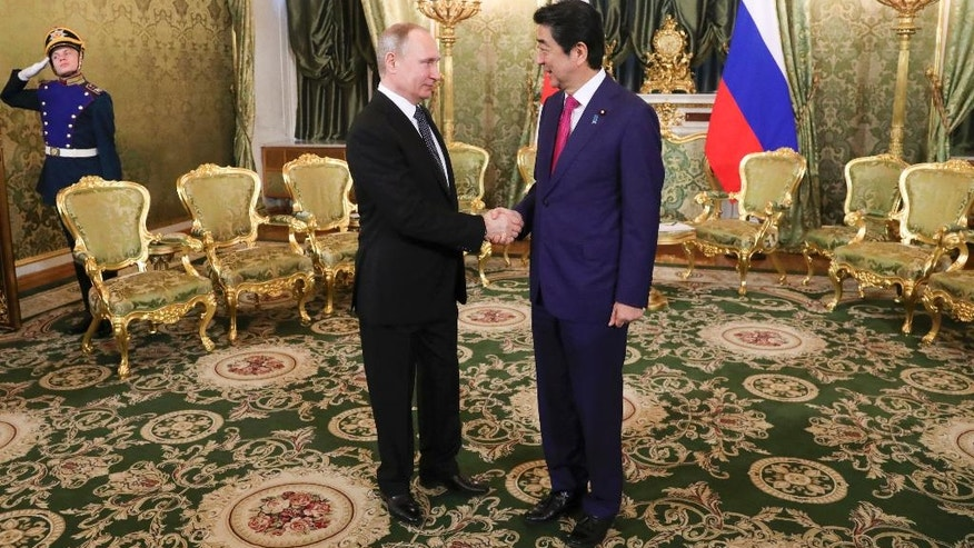 Russian President Vladimir Putin, left, shakes hands with Japanese Prime Minister Shinzo Abe during their meeting in the Kremlin in Moscow, Russia, Thursday, April 27, 2017. Abe visits Moscow on Thursday to meet with President Putin and pursue talks on joint economic projects aimed at a possible breakthrough in their decades-old island dispute. (Mikhail Klimentyev, Sputnik, Kremlin Pool Photo via AP)