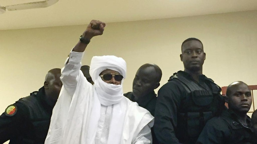 FILE - In this Monday May 30, 2016 file photo, Chad's former dictator Hissene Habre raises his hand during court proceedings in Dakar, Senegal. An appeals court in Senegal has upheld the life sentence for former Chad dictator Hissene Habre on war crimes charges. The court also ruled Thursday April 27, 2017 on an appeal by the more than 4,000 victims that a trust fund be set up to manage reparations awarded to them. Habre has been ordered to pay millions of dollars in compensation. (AP Photo/Carley Petesch, File)