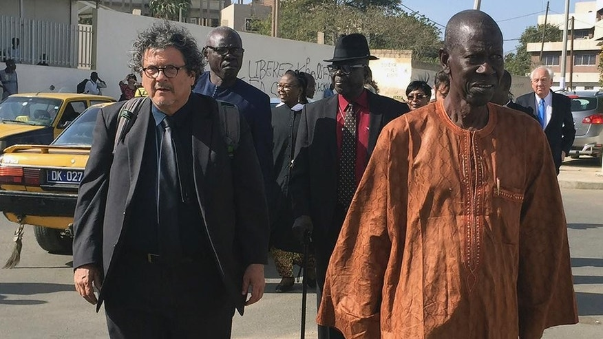 International rights lawyer Reed Brody, left, a member of the International Commission of Jurists who has worked with Chad's former dictator Hissene Habre's victims since 1999, walks with Senegalese victim Abourahmane Gueye, right, following Habre 's appeal in Dakar, Senegal, Thursday April 27, 2017. An appeals court in Senegal has upheld the life sentence of former Chad dictator Hissene Habre on war crimes charges. The court also ruled Thursday that reparations awarded to the more than 4,000 victims be managed by a trust fund. (AP Photo/ Carley Petesch)