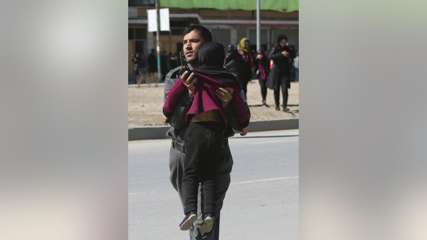 FILE - In this March 1, 2017 file photo, Afghan security police carries a girl after a suicide bombing in Kabul, Afghanistan. Afghanistan's Taliban announced the start of their spring offensive Friday, April 28, 2017, promising to build their political base in the country while focusing military assaults on coalition and Afghan security forces. (AP Photo/Rahmat Gul, File)