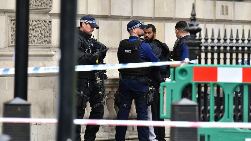 Armed police talk to man at the scene after a person was arrested following an incident in Whitehall in London, Thursday April 27, 2017.  London police arrested a man for possession of weapons Thursday near Britain's Houses of Parliament. (Dominic Lipinski/PA via AP)