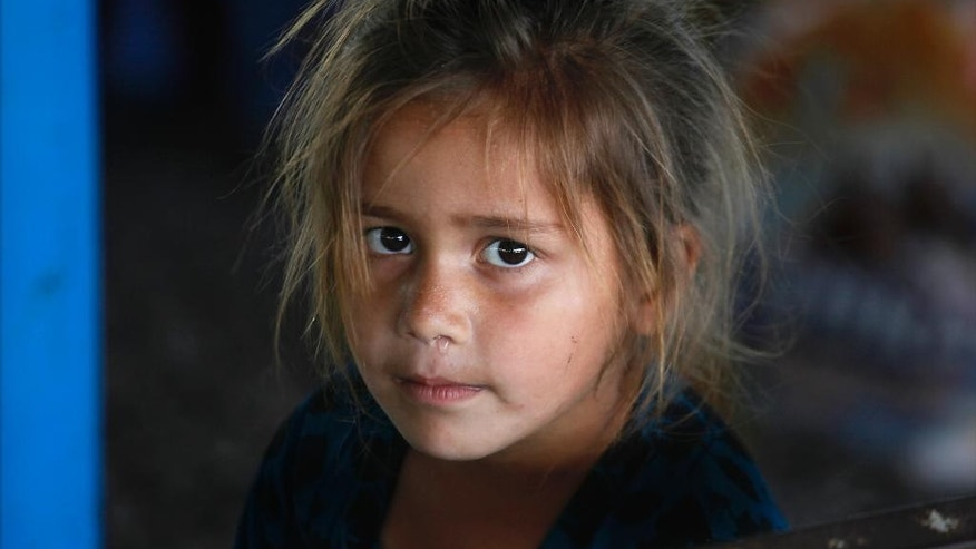 An Afghan refugee girl waits with her family at the office of United Nations High Commissioner for Refugees to register to go back to Afghanistan, in Peshawar, Pakistan, Thursday, April 27, 2017. The United Nation reported Thursday that there has been a slight drop in the number of civilians dying in Afghanistan's protracted 16-year war during the first three months of this year. According to the report there is also an unprecedented number of Afghans displaced by war living inside the country and there are another 1.5 million Afghans living as refugees in neighboring Pakistan. (AP Photo/Muhammad Sajjad)