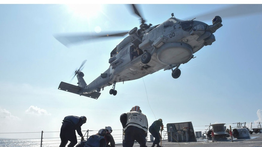 U.S. Navy Sailors participate in a medical training exercise on the deck of the Arleigh Burke-class guided missile destroyer USS Lassen (DDG 82) with an MH-60R Seahawk helicopter, in the South China Sea, October 28, 2015, provided by the U.S. Navy.