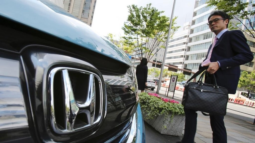 A man walks past a Honda car on display at Honda Motor Co. headquarters in Tokyo, Friday, April 28, 2017. Honda Motor Co. is reporting a 95.9 billion yen ($864 million) profit for January-March, a reversal from the 93.4 billion yen loss it racked up a year earlier, as the Japanese automaker recovers from costs for a massive air-bag recall. (AP Photo/Koji Sasahara)